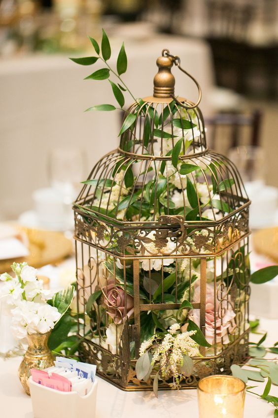 a metallic cage with foliage and lush florals for a beautiful wedding centerpiece