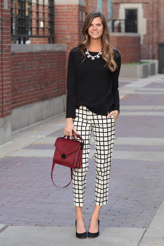 a black top, a statement necklace, windowpane cropped pants and a burgundy bag