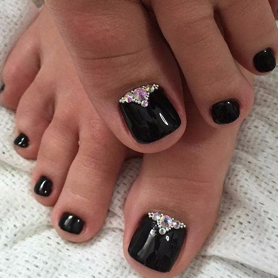 glossy black nails are a great choice for Halloween, accentuate them with rhinestones