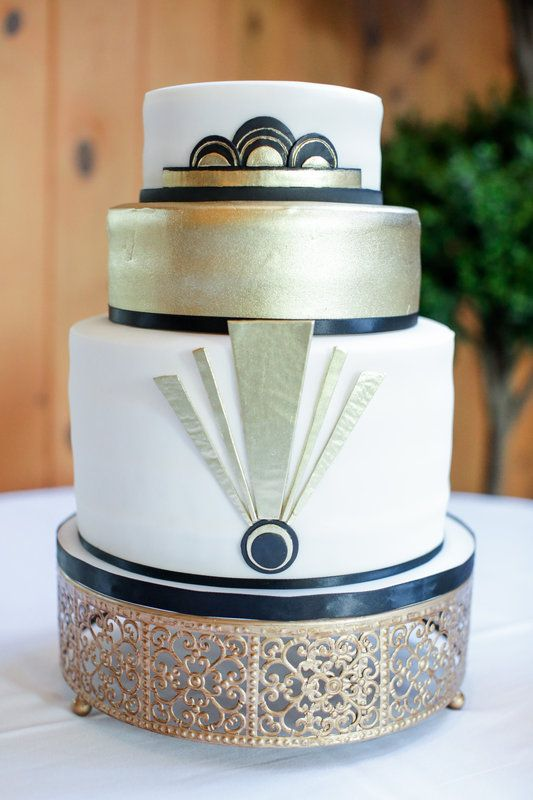 a black, white and gold wedding cake with scallops and geo decor