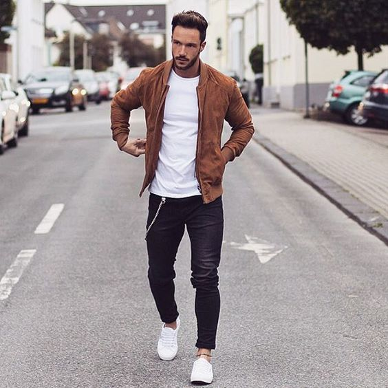 an amber suede bomber jacket, black jeans, a white tee and white sneakers