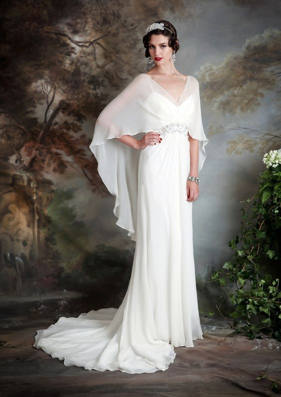 an ivory wedding dress with spaghetti straps and a ruffled cape attached to the embellished belt