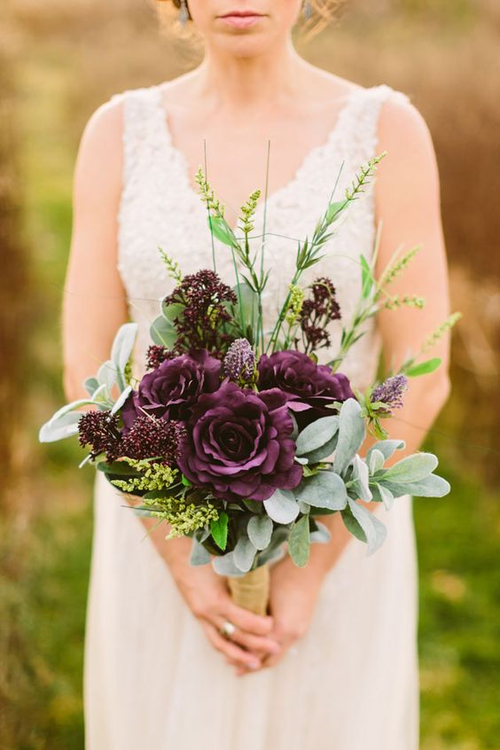a moody fall bouquet with greenery and deep purple roses and blooms