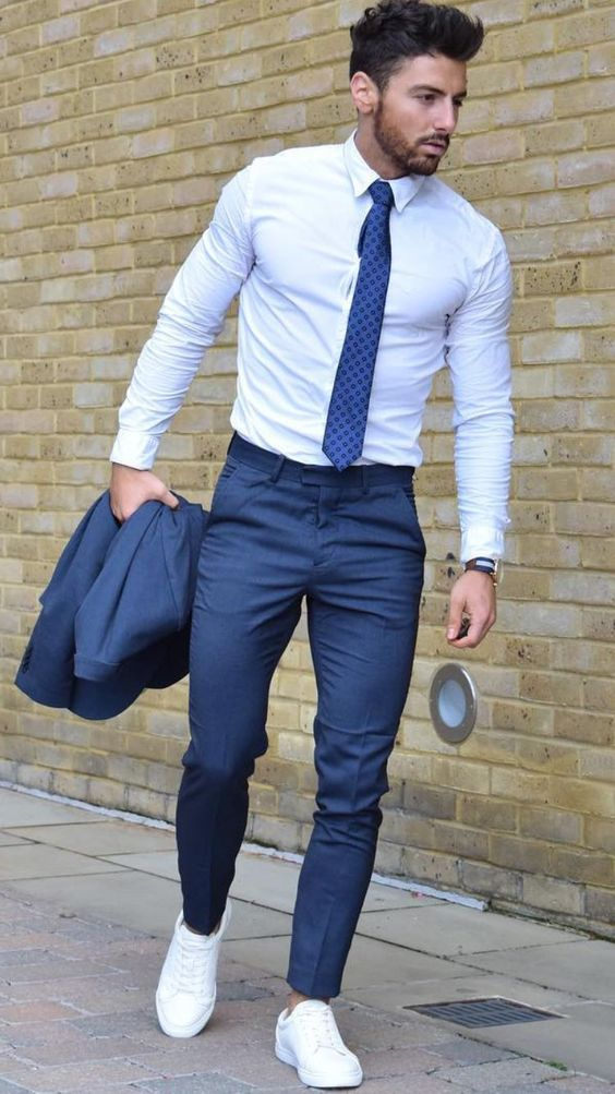 a navy suit, a neutral shirt, a blue tie and white sneakers to go to work