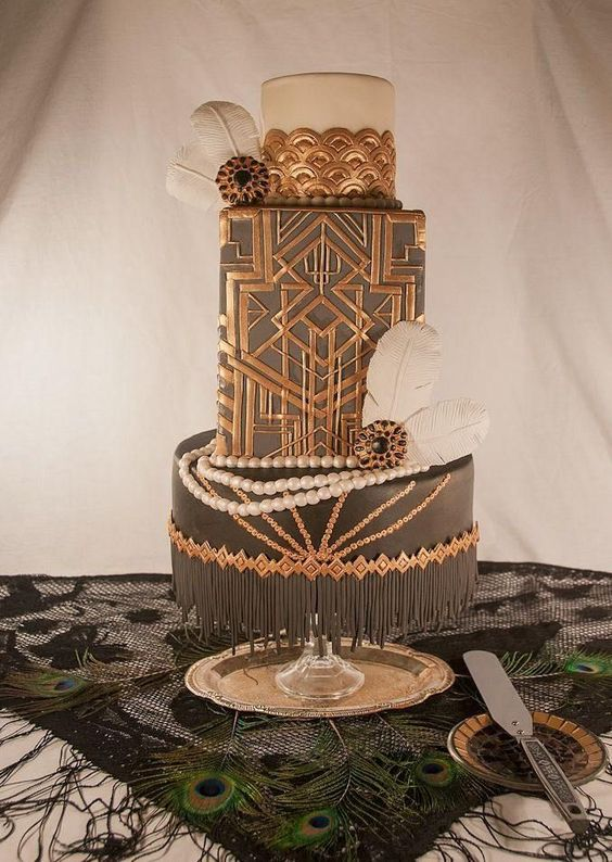 a black and copper wedding cake with geo decor, scallops and feathers