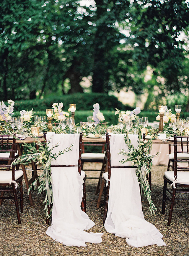 The wedding chairs were decorated with flowy fabric and greenery