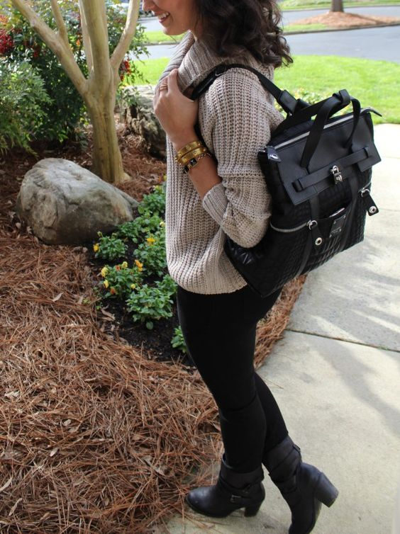 a neutral chunky knit sweater, black leggings, black booties and a black backpack