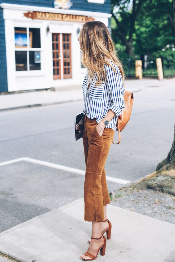 a striped white and black shirt, amber suede cropped pants, matching shoes and a backpack