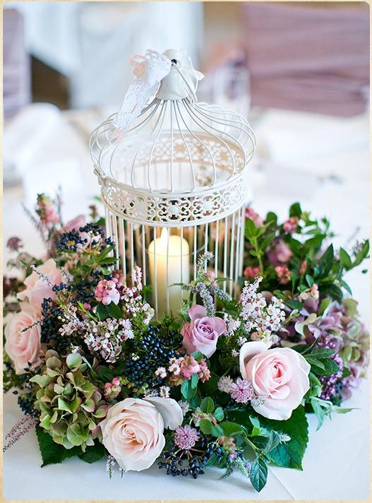 a cage used as a candle holder and surrounded with lush lilac blooms and greenery