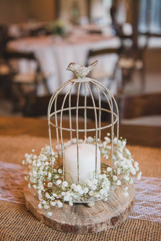 a small vintage cage with a bird on top placed on a wooden slice, a candle and baby's breath