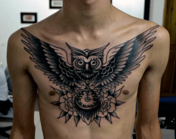 Black owl and clock tattoo on the chest