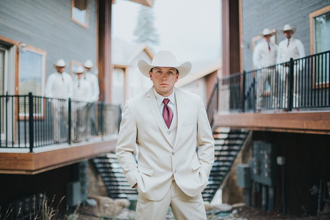 The groom was wearing a neutral suit, a burungdy tie and a cowboy hat