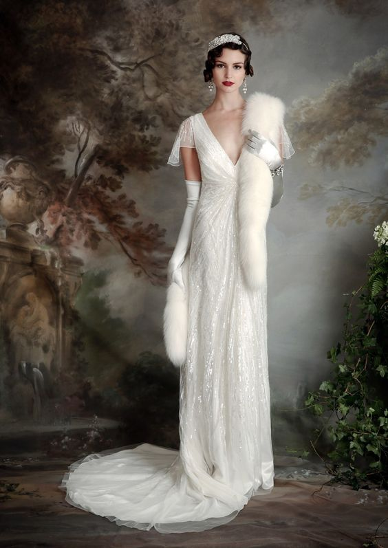 sparkling wedding dress with a deep V-neckline and cap sleeves, a small train and a faux fur shawl