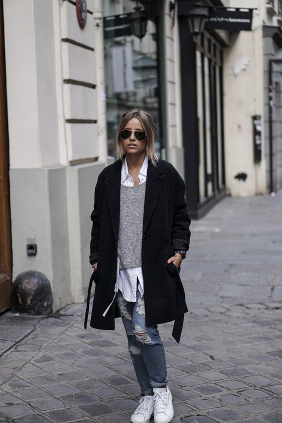 ripped jeans, a grey sweater, a white shirt, whit sneakers and a black coat