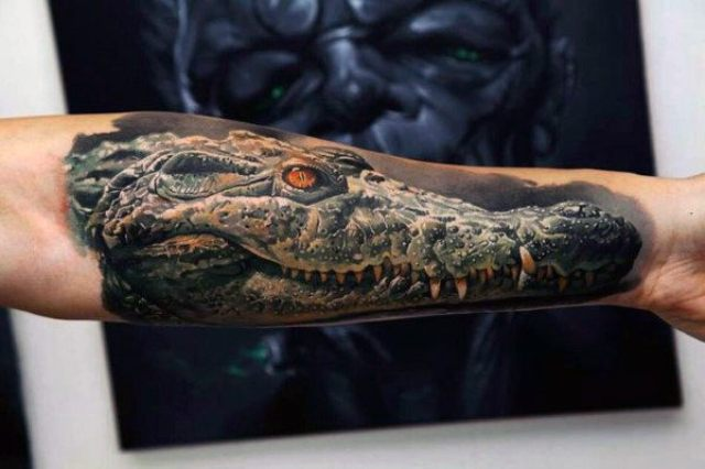 Dangerous alligator tattoo on the hand