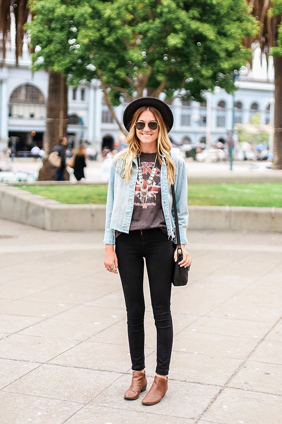 black skinnies, a printed tee, brown booties, a cropped distressed denim jacket and a hat