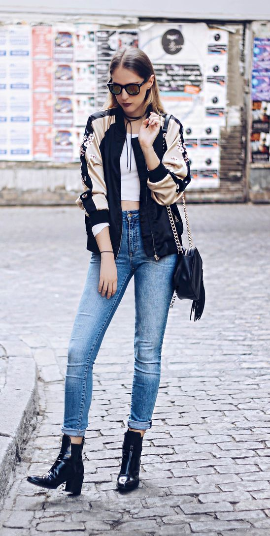 high waist blue jeans, a crop top, an embroidered bomber jacket and black leather boots