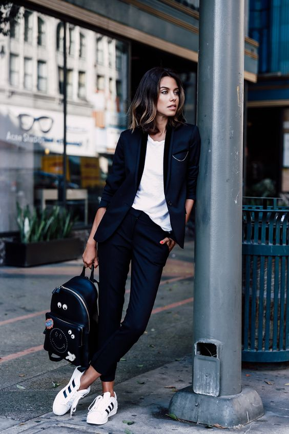 a black tuxedo with cropped pants, a white tee, white sneakers and a black backpack