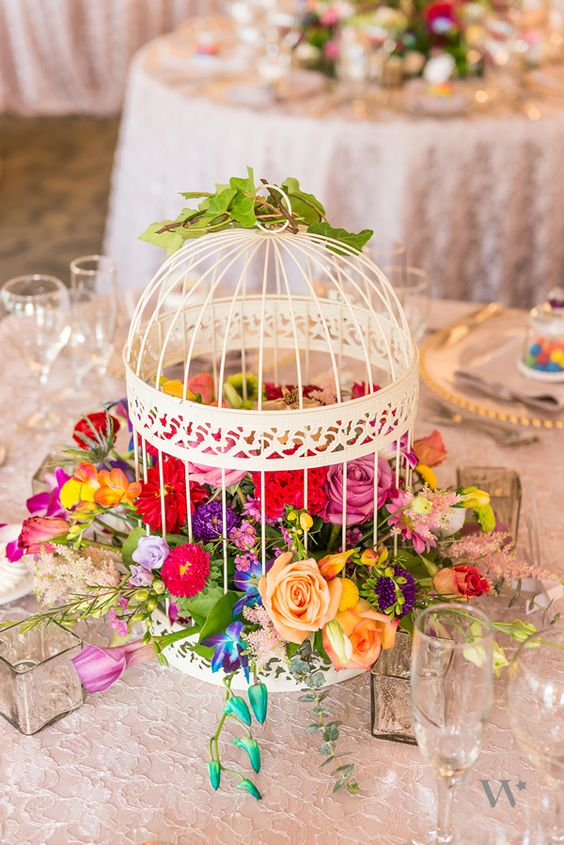 a decorative white cage filled with lush and bold florals for a summer garden wedding