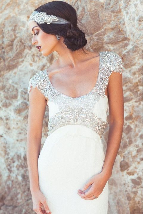 a deep scoop neckline wedding gown with a heavily embellished neckline and waistline, cap sleeves