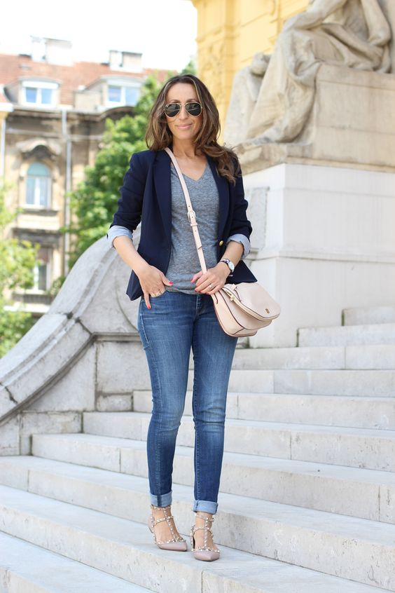 blue jeans, a grey tee, a navy blazer and nude spiked flats