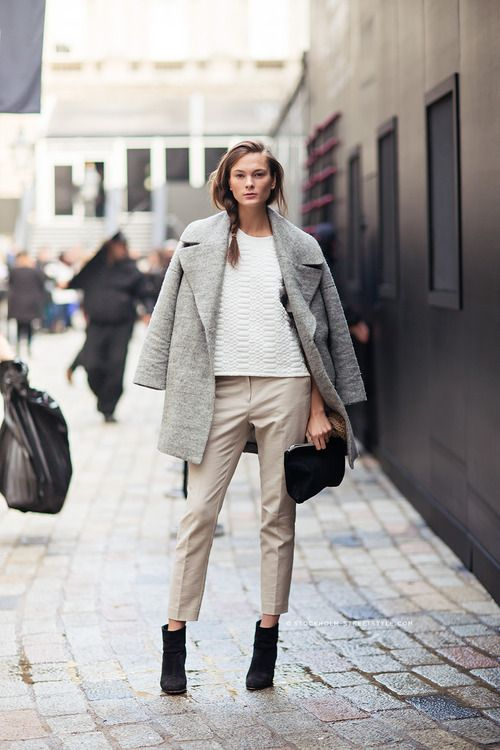 neutral cropped pants, black suede boots, a white textural top, a grey coat and a black clutch