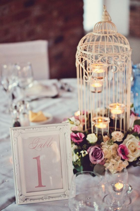 a white cage with tealights and bold blooms that surround the cage