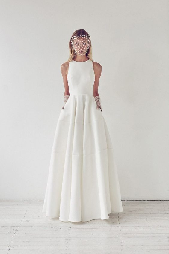minimalist halter neckline A-line wedding dress with pockets, a birdcage veil and gloves