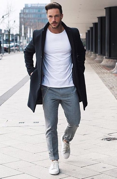a white tee, grey pants, white sneakers and a black coat
