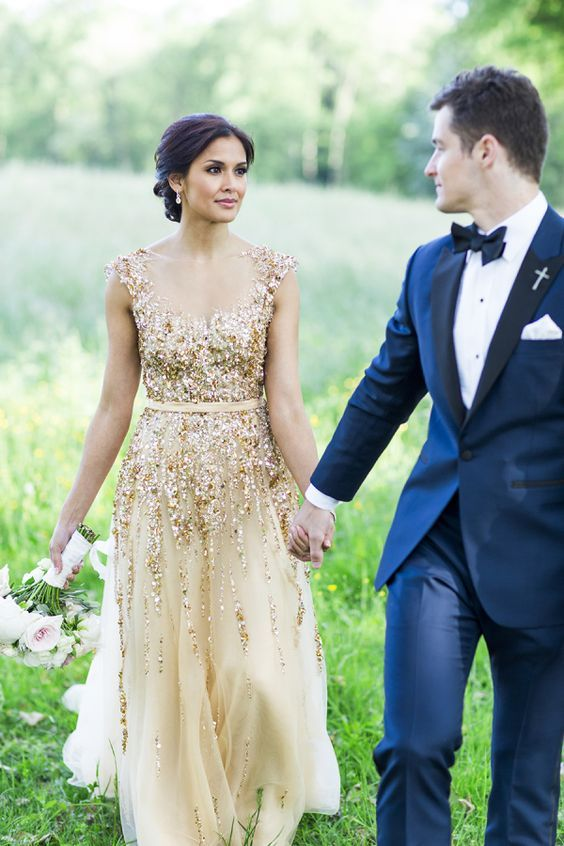 the groom in a navy suit with a bow tie and the bride in a gold glitter wedding gown