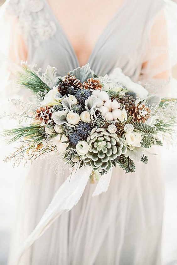 a gorgeous bouquet with snowy pinecones, thistles, succulents, evergreens and white cotton