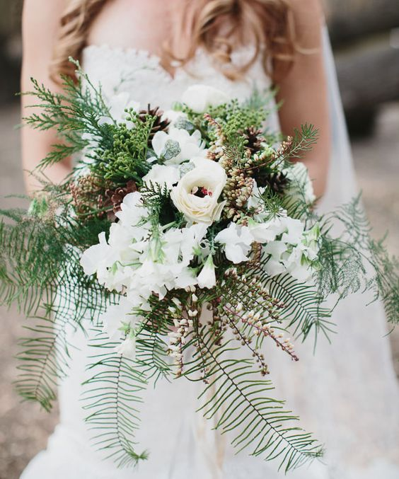 a neutral bouquet with white blooms, evergreens, foliage and pinecones