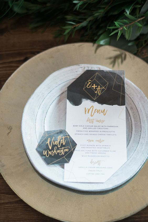 a modern menu and place cards done with dark watercolor and gold touches for a chic modern wedding