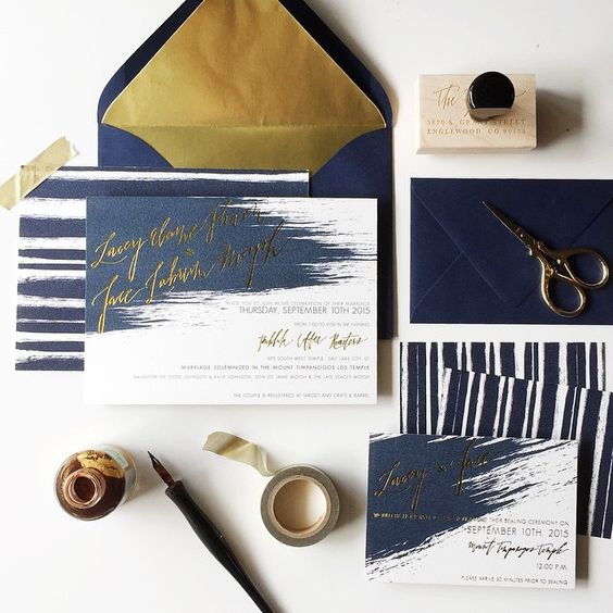 a navy and gold foil wedding staitonery set with brushstrokes and stripes looks unusual and modern