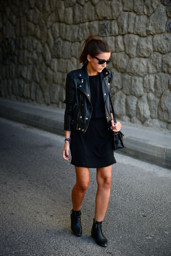 a black dress, black leather booties, a cropped black leather jacket and a bag