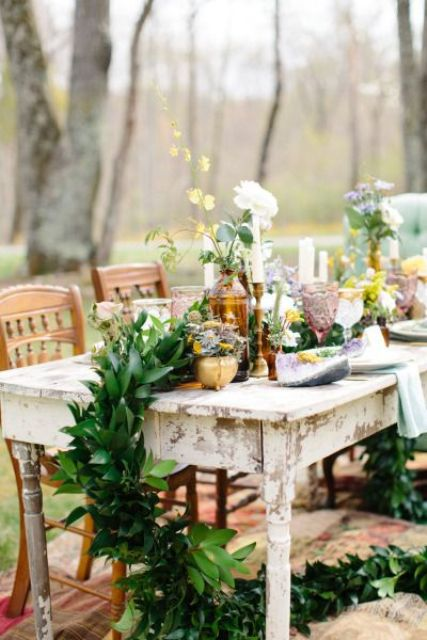 a lush greenery table runner with bold blooms and gilded candle holders for an eclectic tablescape