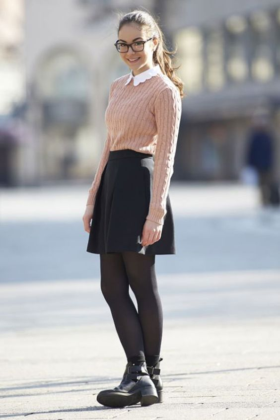 a blush sweater over a white shirt, a black skirt, black tights and boots