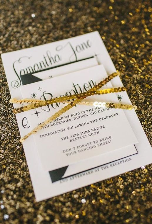 a modern black and white invitation set wrapped with gold sequins
