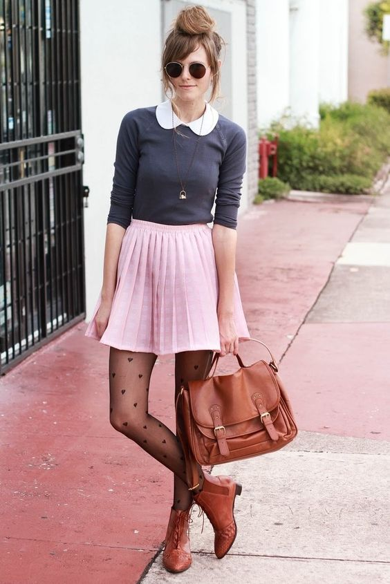 a grey top, a pink pleated skirt, heart print tights, brown booties and a bag