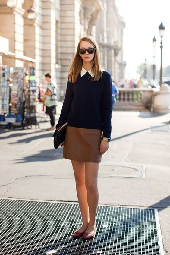 a navy sweater over the shirt, a brown leather skirt, red flats and a clutch