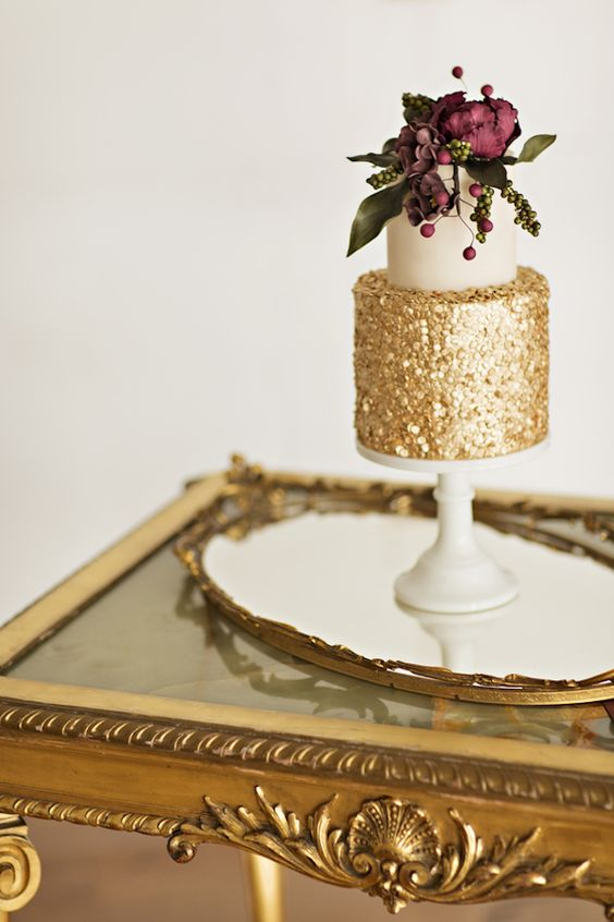 a wedding cake with a white and gold layer, with greenery and burgundy blooms on top