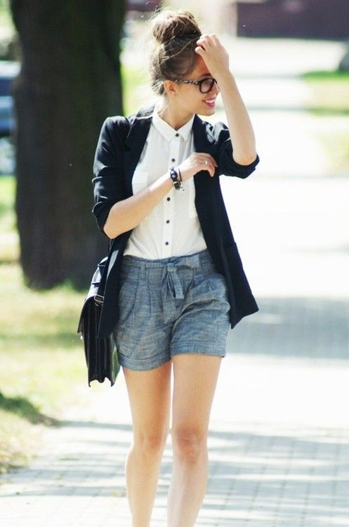 grey shorts, a white shirt with black buttons, a black blazer and a bag