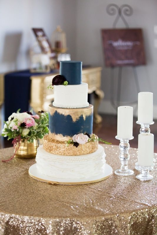 a wedding cake with navy and gold glitter layers and whites for a contrast
