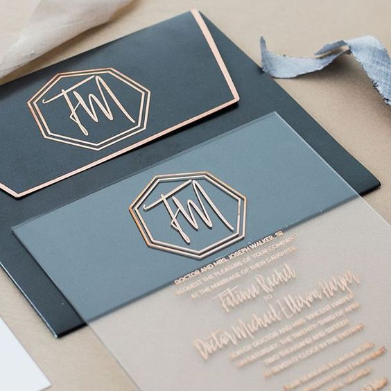 a stylish acrylic invitation with copper letters and a matching black envelope