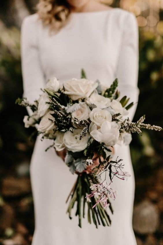 a modern bouquet with white roses, evergreens and foliage for a textural look