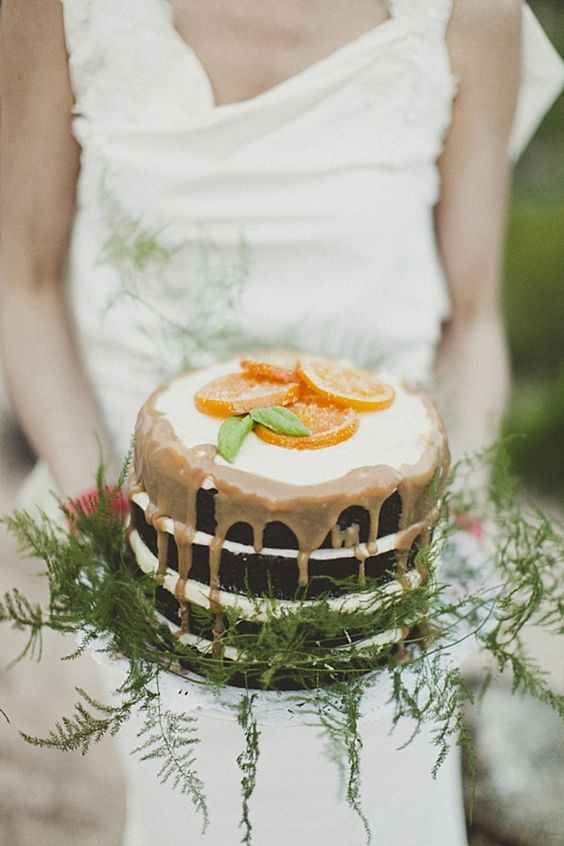 a naked wedding cake with caramel dripping, ferns and citrus slices