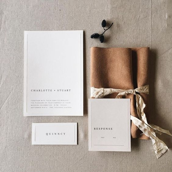 neutral wedding invitations wrapped with faux leather to add an eye-catchy touch