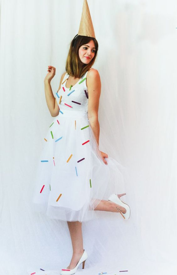an ice-cream cone costume of a flowy white sleeveless dress with cofetti attaached, white shoes and a cone hat
