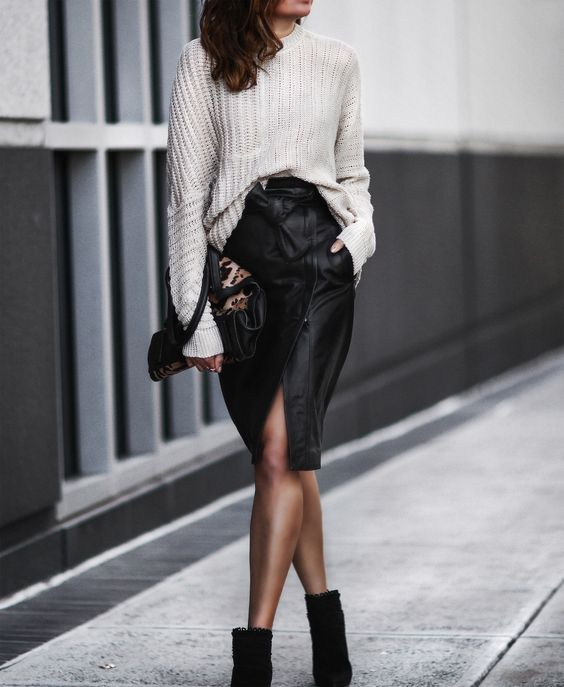 black suede booties, a white oversized sweater, a black leather skirt with a slit