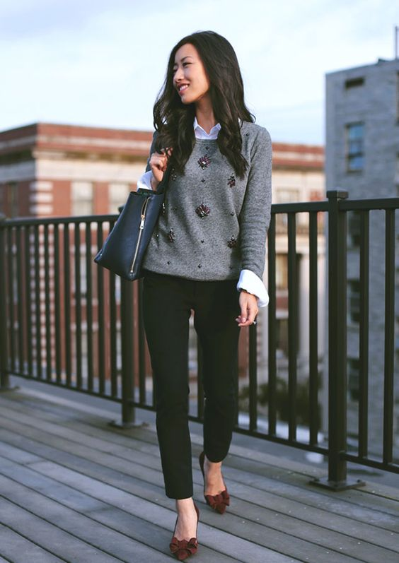 black jeans, a white shirt, a grey embellished sweater and burgundy bow shoes